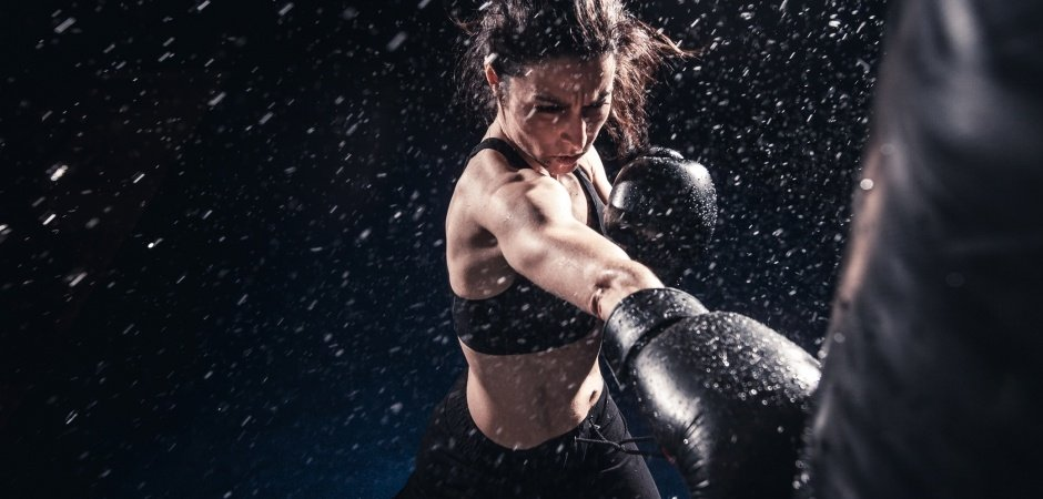 woman fiercely hitting a punching bag